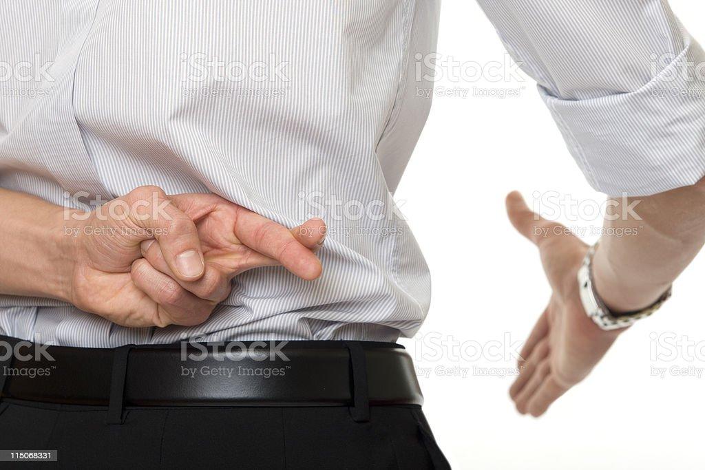crossed fingers at handshake stock photo