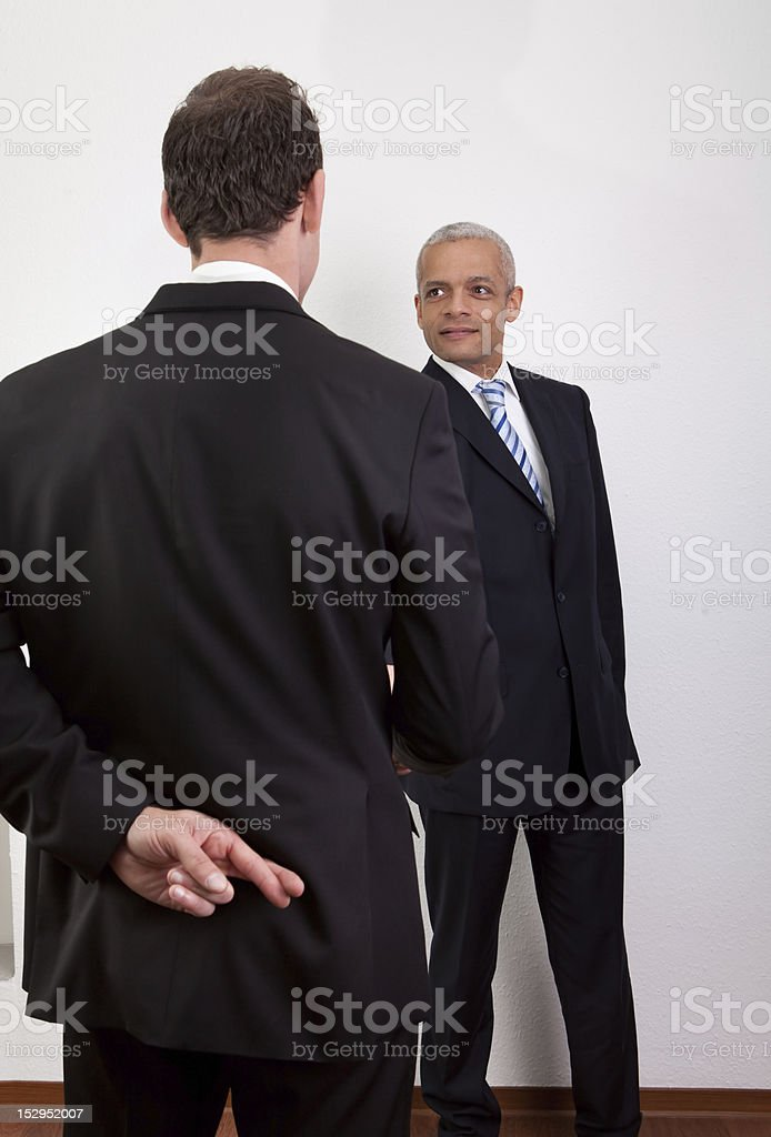 Crossed Fingers At Handshake royalty-free stock photo