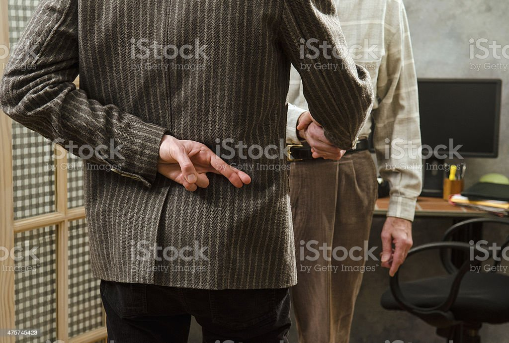 crossed fingers while shaking hands stock photo