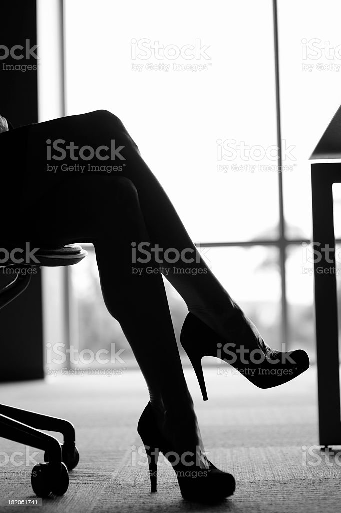 Crossed legs with high heels in the office stock photo