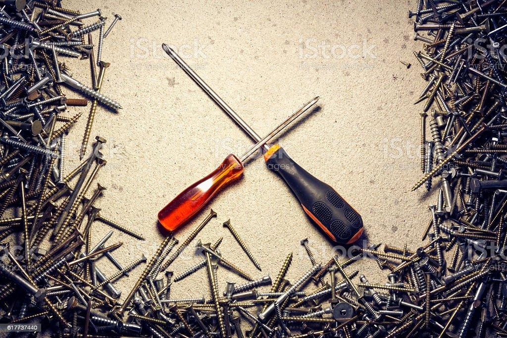 Crossed screwdrivers framed by screws stock photo