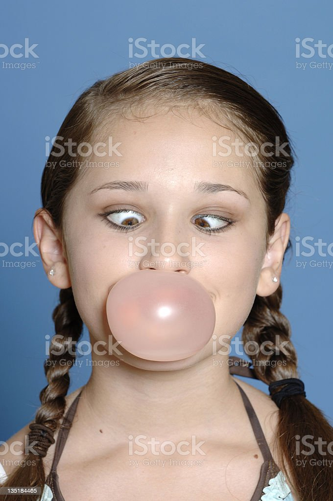 cross-eyed girl blows bubble with bubble gum royalty-free stock photo