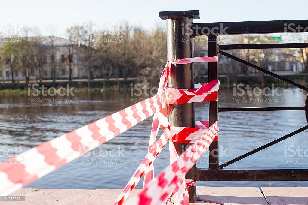 crossing barrier tape blocking the way to the river stock photo