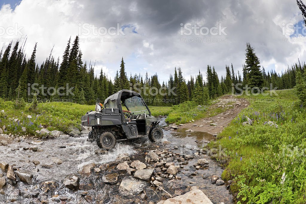 UTV crossing creek stock photo
