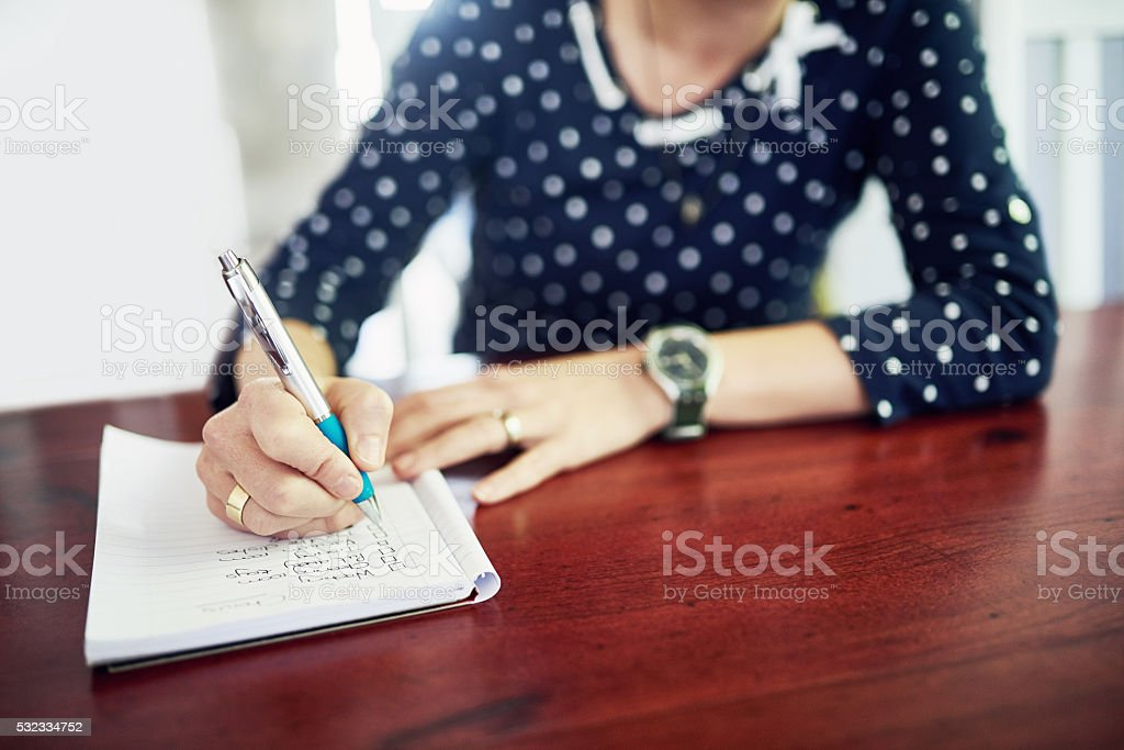 Crossing off tasks from her to do list stock photo