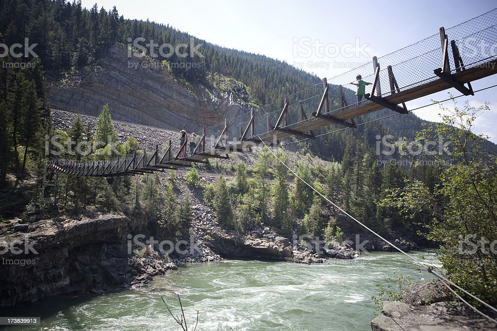 crossing the rope bridge royalty-free stock photo