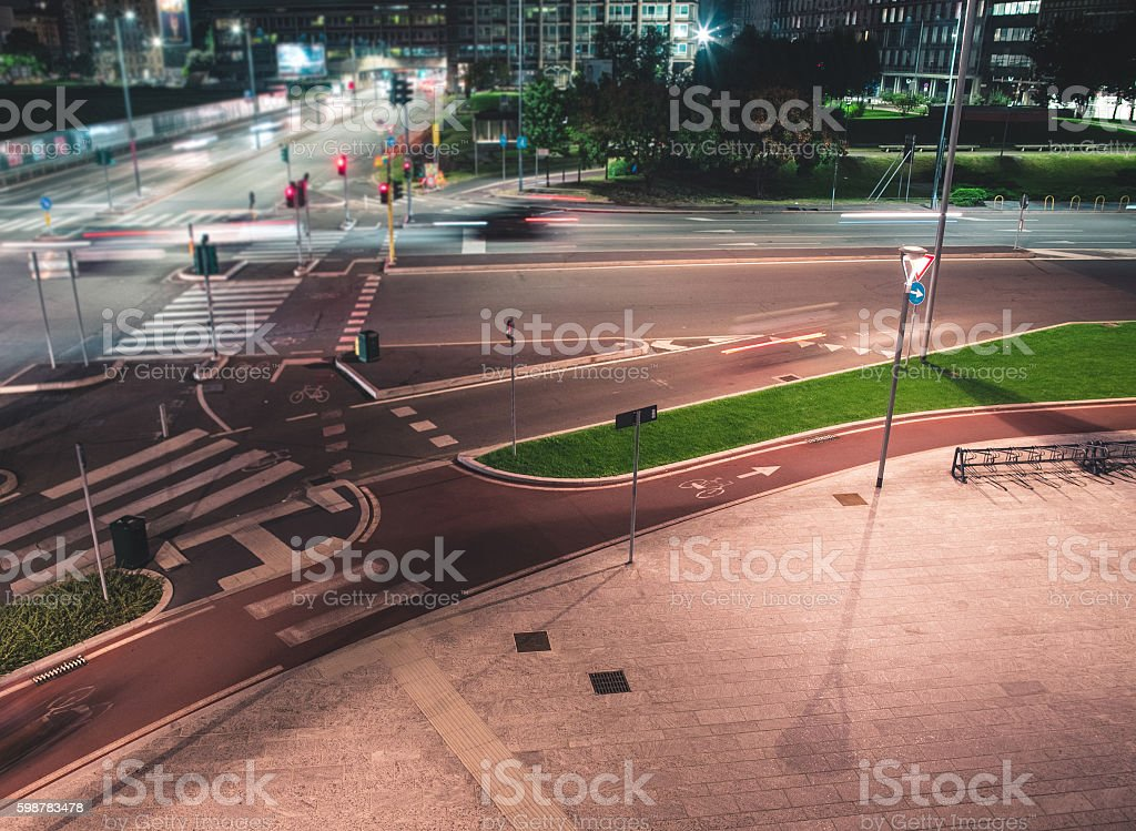 Crossroad and fast vehicles in the modern city by night stock photo