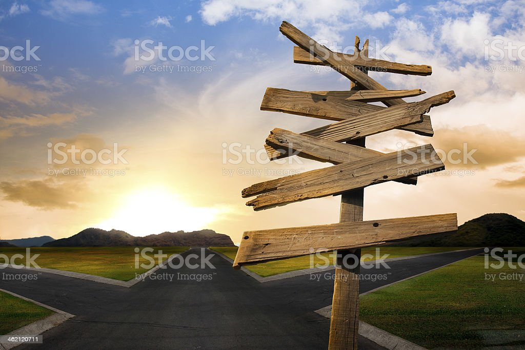 crossroads with confusing directional arrow sign stock photo