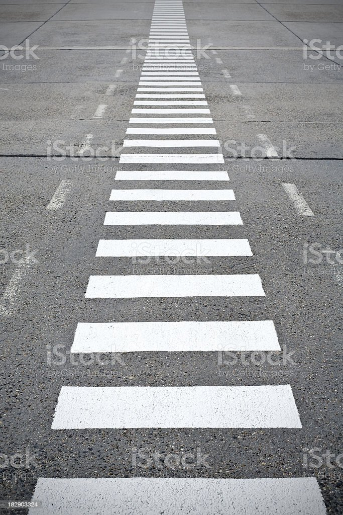 Crosswalk - road marking on weathered asphalt royalty-free stock photo