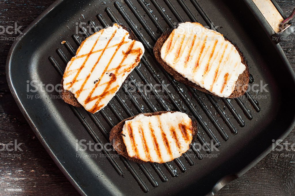 Crostini with fried cheese on the grill stock photo