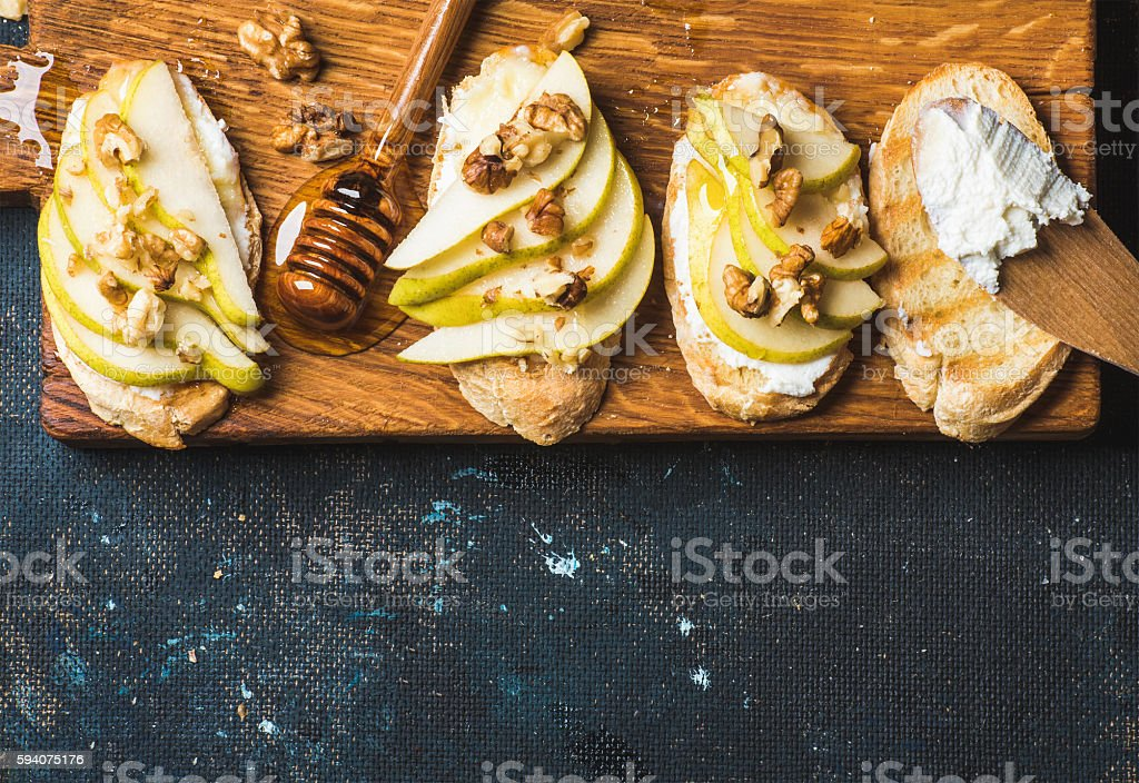 Crostini with pear, ricotta cheese, honey and walnuts stock photo