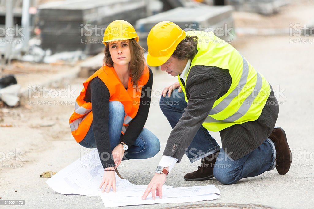 Crouching architects with blueprints at construction site stock photo