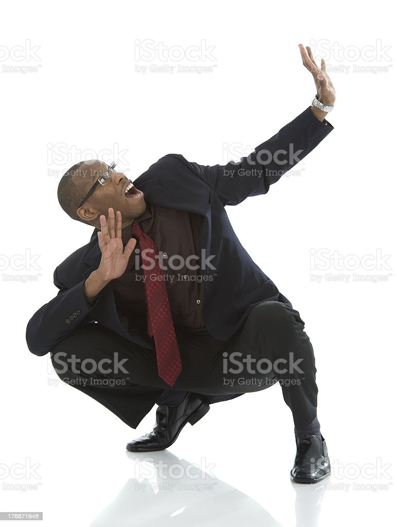 Crouching Black Business Man Cowering in Fear stock photo