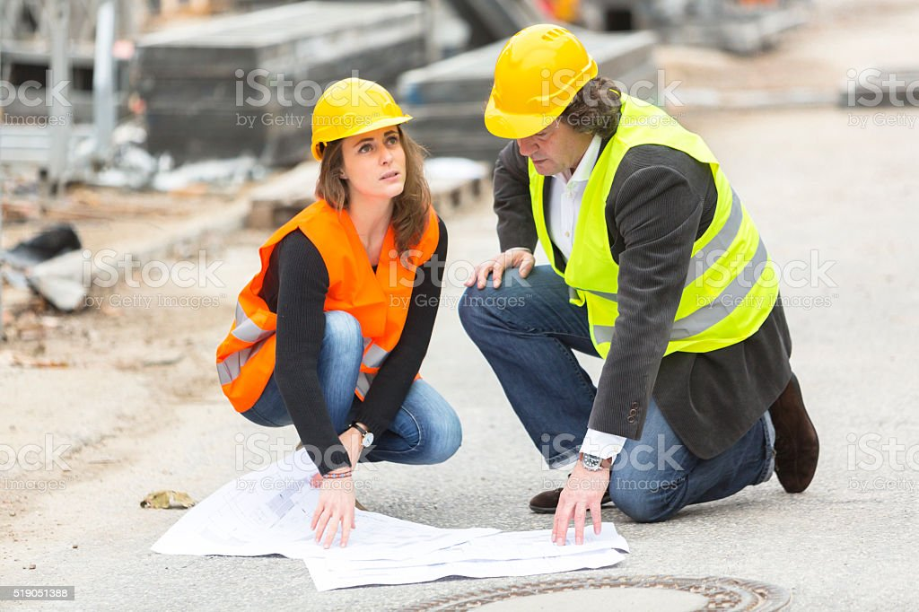 Crouching engineers with blueprints at construction site stock photo