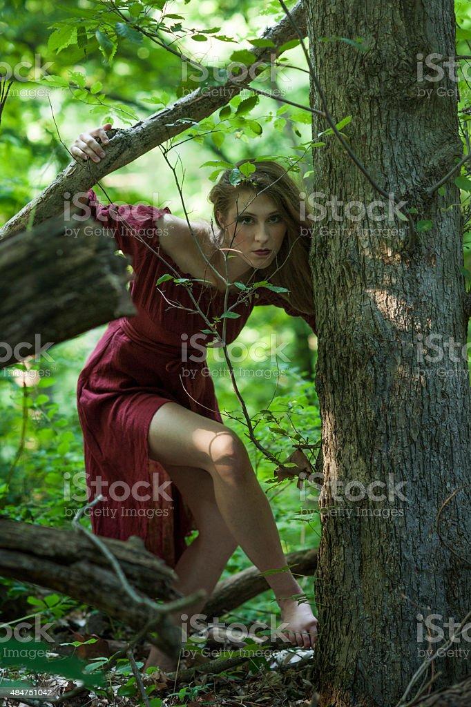 Crouching woman advances barefoot through grapevines stock photo