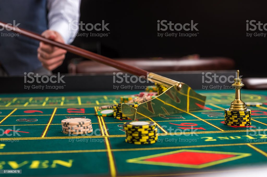 Croupier collects chips using stick in casino. stock photo