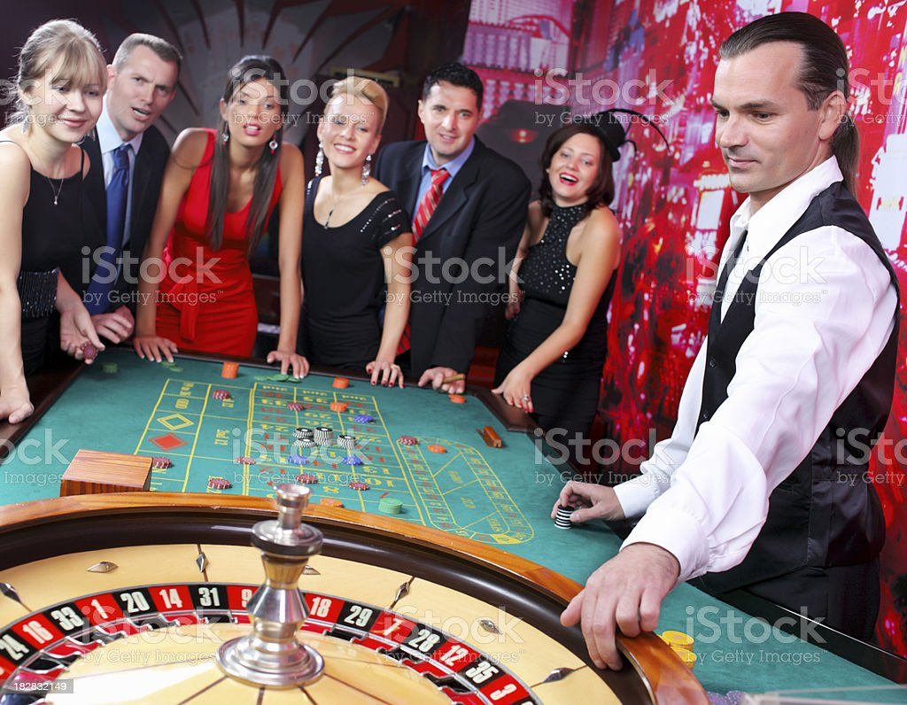 Croupier is spinning the roulette, while gamblers are waiting an stock photo