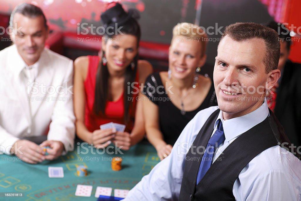 Croupier looking at camera, behind his gamblers playing Blackjac stock photo