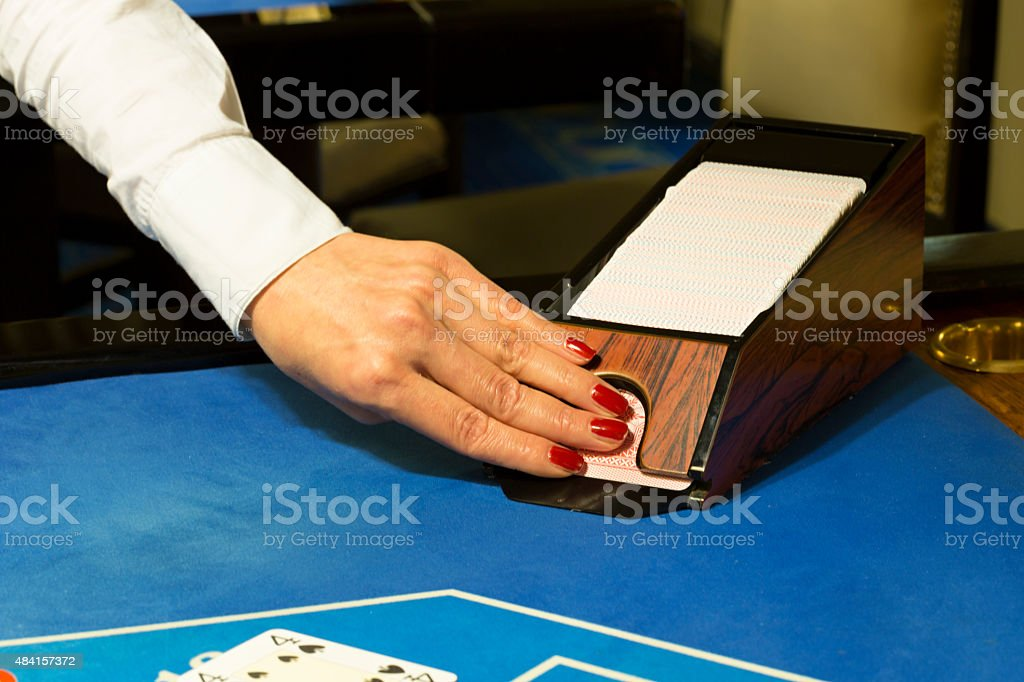 Croupier pulling out cards from box at blackjack table stock photo