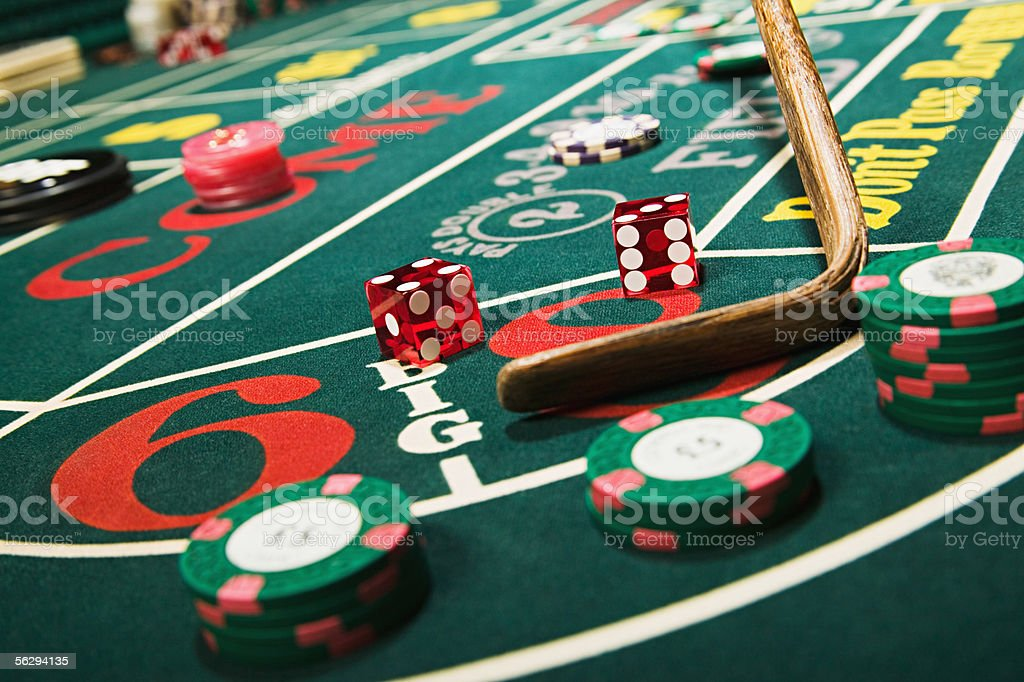 Croupier stick clearing craps table stock photo