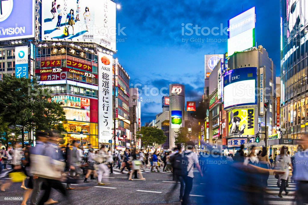 Crowd against buildings with advertisements stock photo