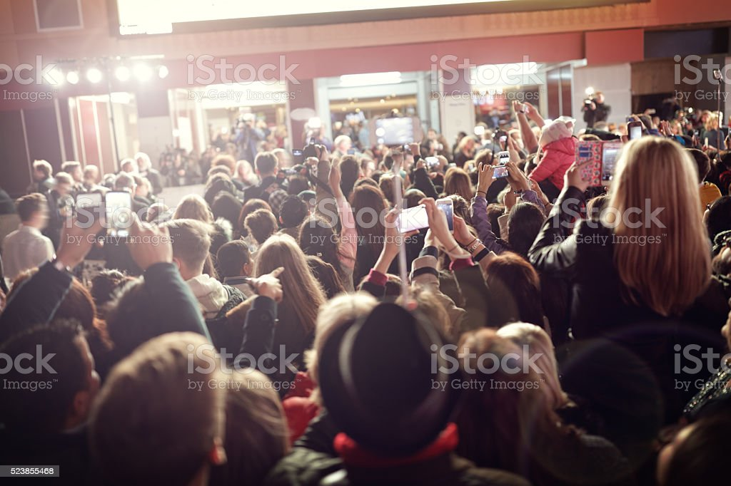 Crowd and fans taking photographs on mobile phones at a red carpet...
