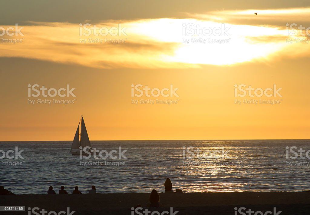 Crowd and Sailboat at Sunset stock photo