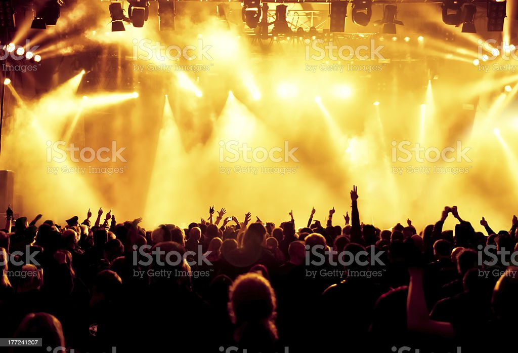 A crowd at a concert with yellow lights and fog stock photo