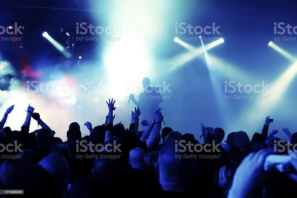 Crowd at concert waving hands under blue stage lights royalty-free stock photo
