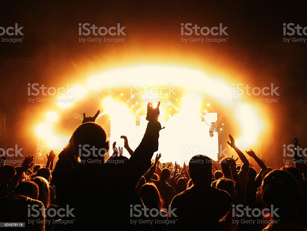 Crowd at rock concert in front of illuminated stage stock photo