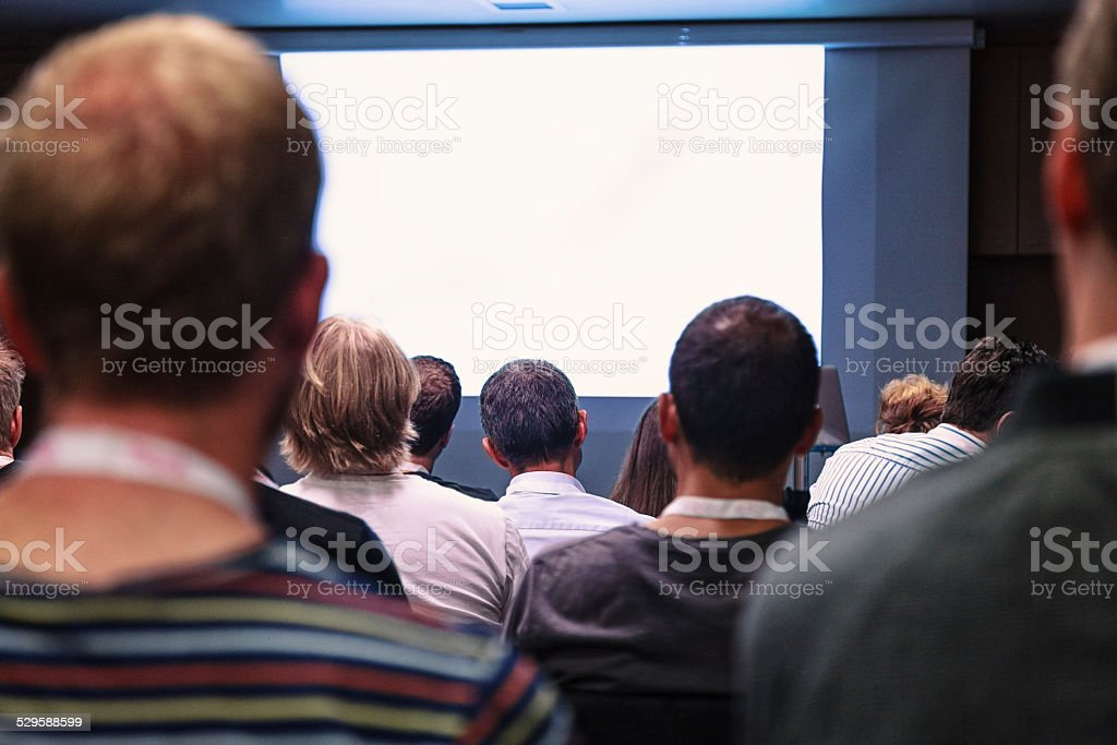 Crowd audience looking at blank screen stock photo