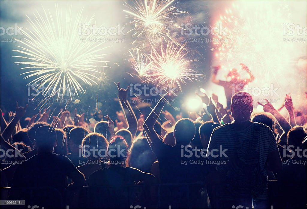 Crowd celebrating with fireworks stock photo