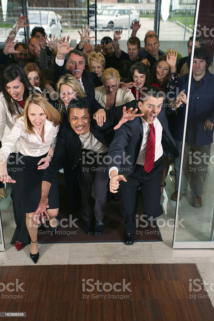 Crowd coming through open door stock photo