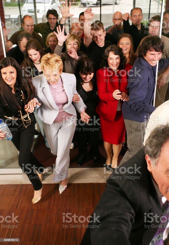 Crowd coming through open door stock photo