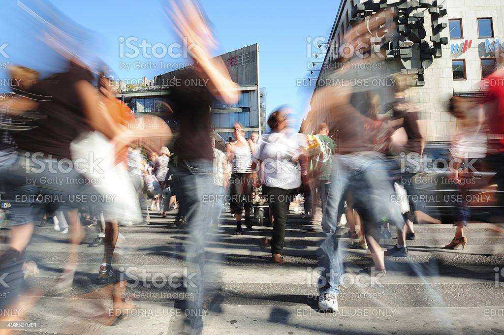 Crowd crossing sunlit street, motion blur stock photo