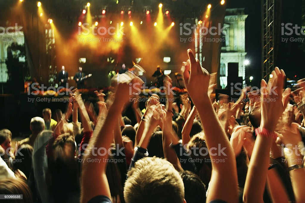 Crowd holding hands up against concert stage stock photo