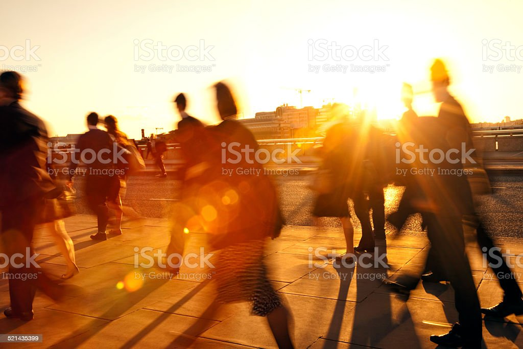 Crowd of Blurred Commuters in Rays of Setting Sun stock photo