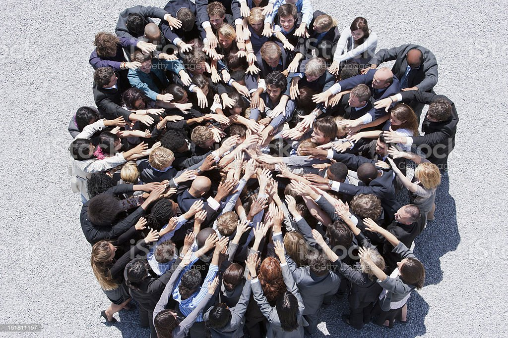 Crowd of business people forming huddle with extended arms stock photo