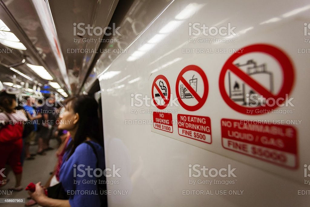 Crowd of Commuters and Prohibition Signs in Singapore stock photo
