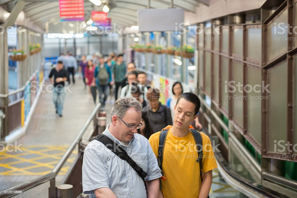 Crowd of Commuters Riding Mid-Levels Escalator in Hong Kong stock photo