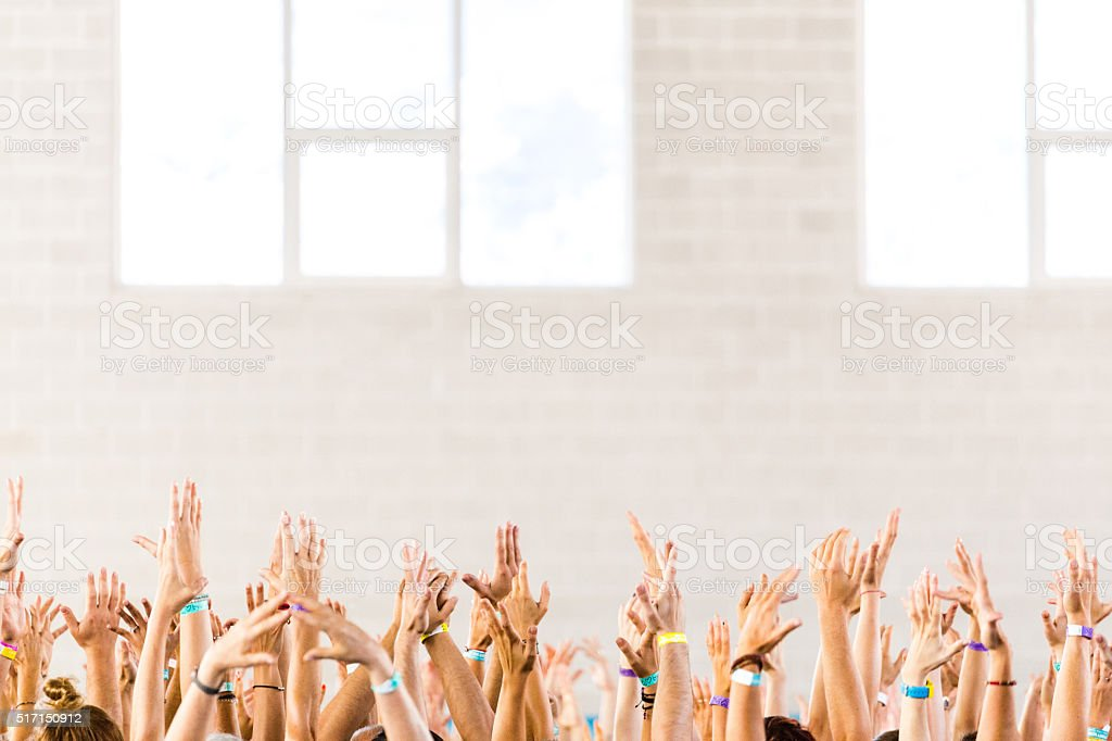crowd of hands lifted up at a yoga class stock photo