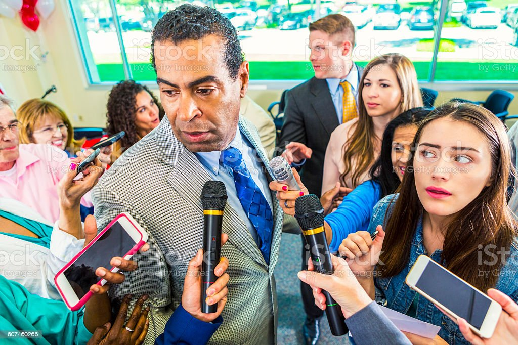 A crowd of journalists surround political candidate stock photo