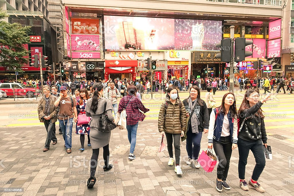Crowd of multiracial people crossing Nathan Road in Hong Kong stock photo