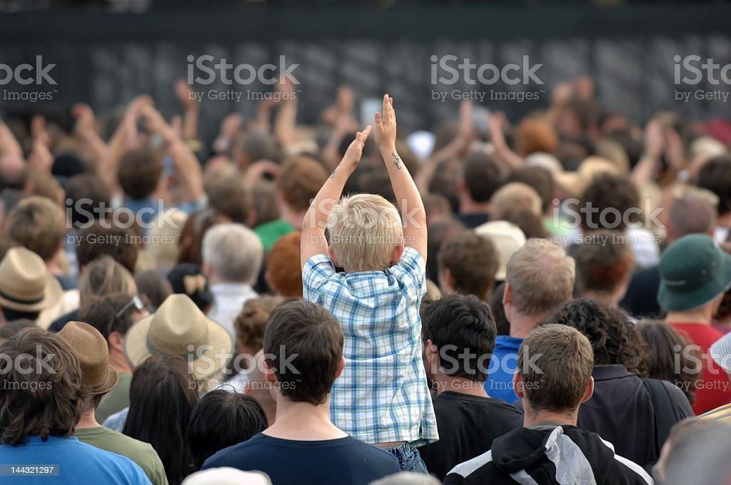 Crowd of people at a music festival from behind royalty-free stock photo