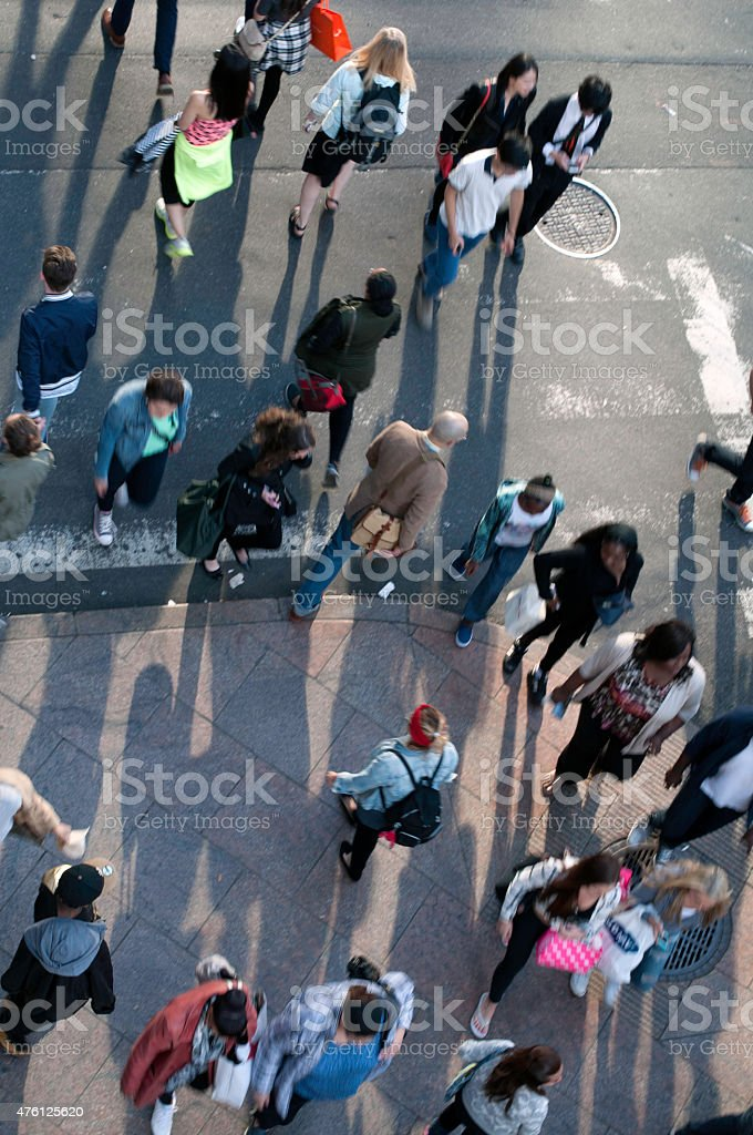 Crowd of people crossing a city street stock photo