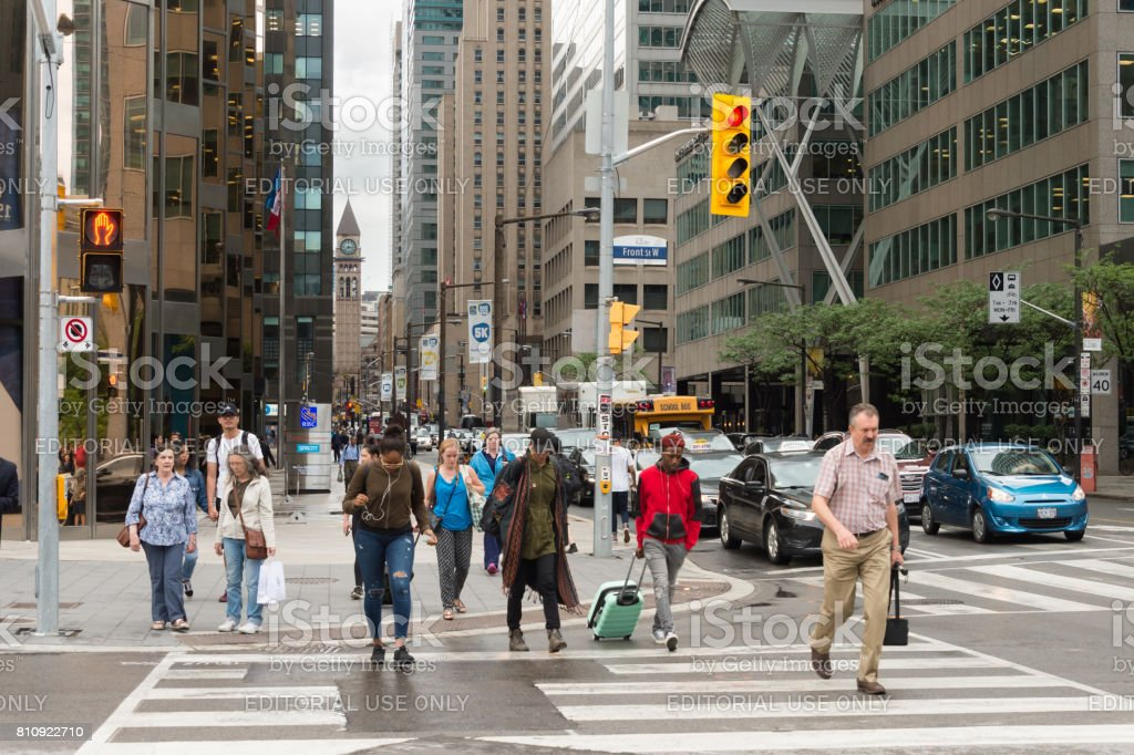 A crowd of people crossing Front street in Downtown Toronto