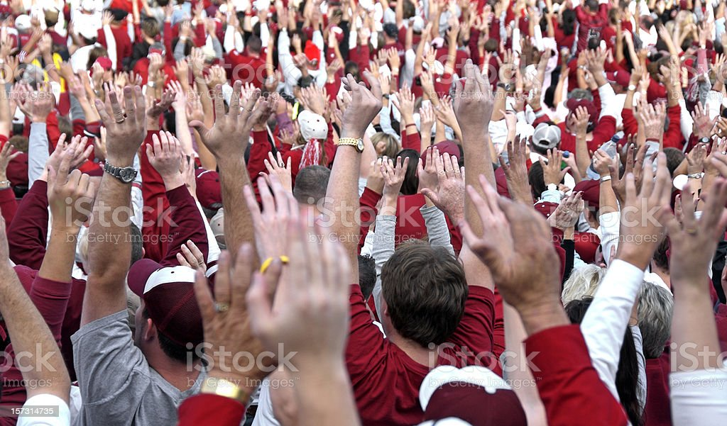 A crowd of people dressed in red with their hands raised royalty-free stock photo