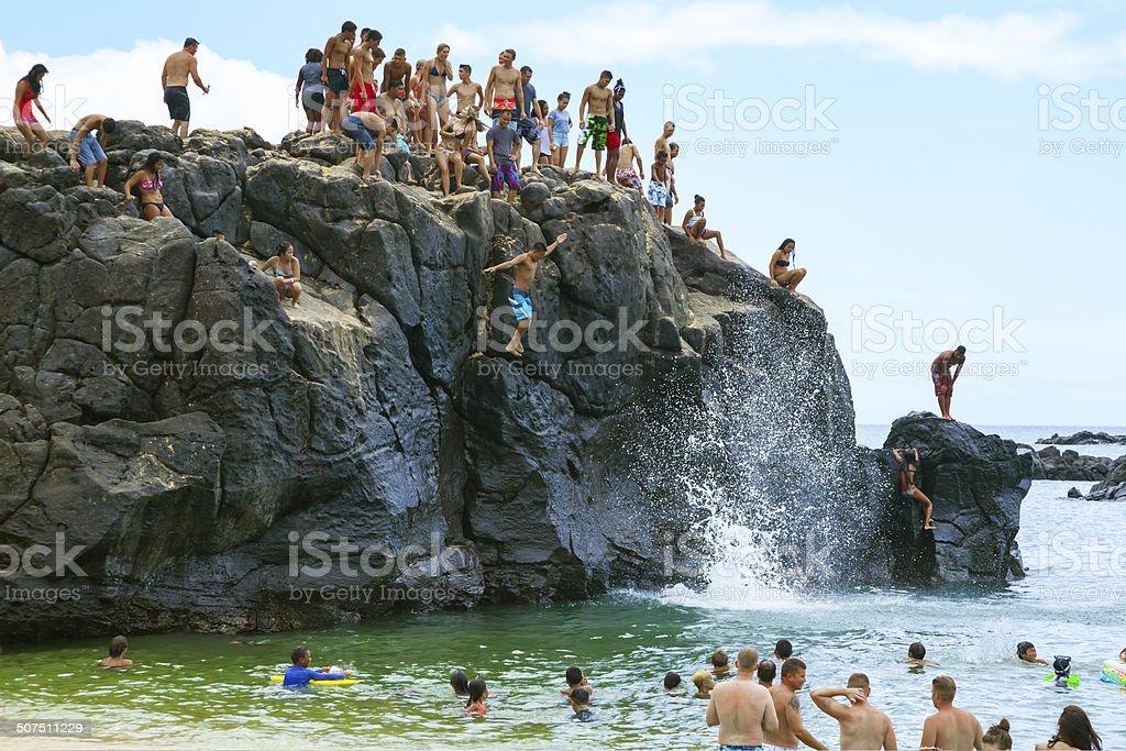 Crowd of people enjoys Jump Rock, Waimea Bay, Oahu Hawaii stock photo