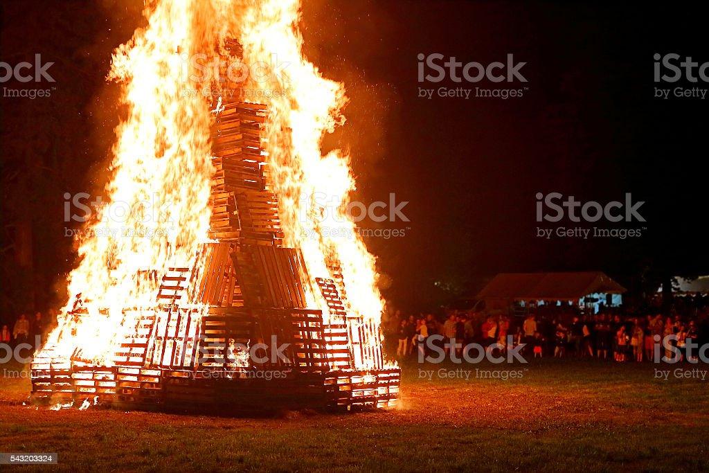 Crowd of people meeting around big bonfire in summer stock photo