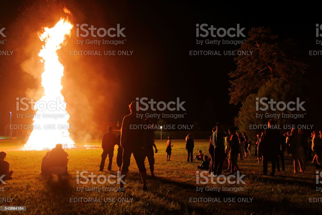 Crowd of people meeting around big bonfire in summer stock photo